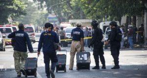 Petugas menyisir lokasi ledakan bom yang terjadi di tiga lokasi di Surabaya, Minggu (13/5/2018) [AFP]