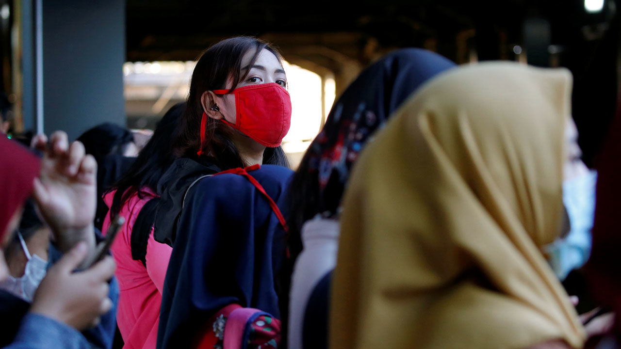 Woman wearing protective mask looks on as she waits for a commuter train at a station in Jakarta